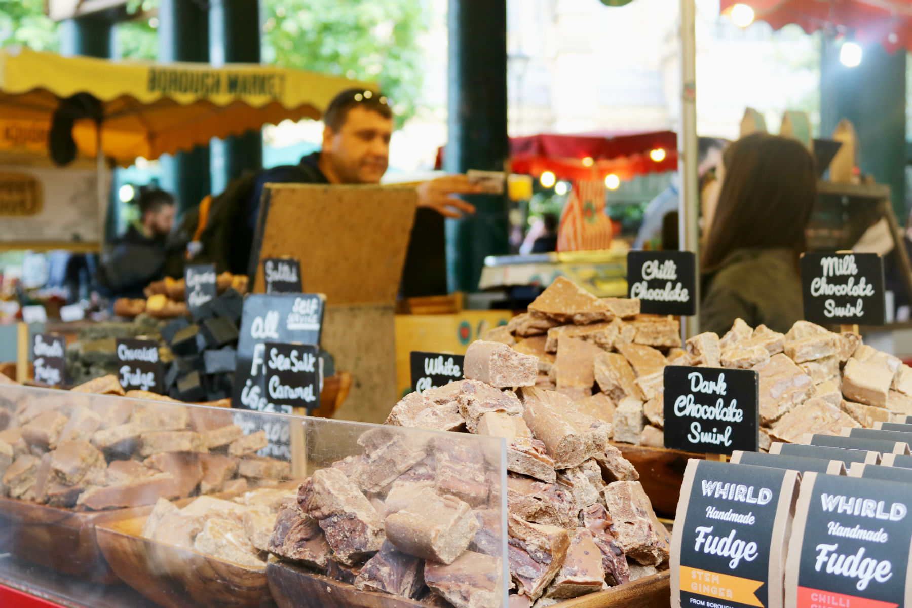 Man handing money over at a chocolate stall in Borough Market, London