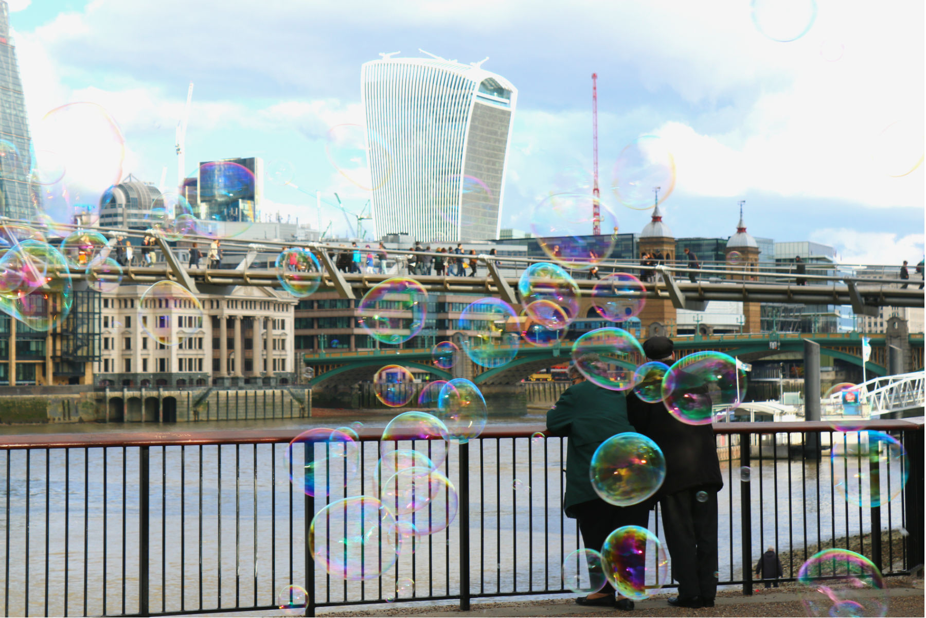 Old couple looking towards Millennium Bridge with bubbles in the foreground