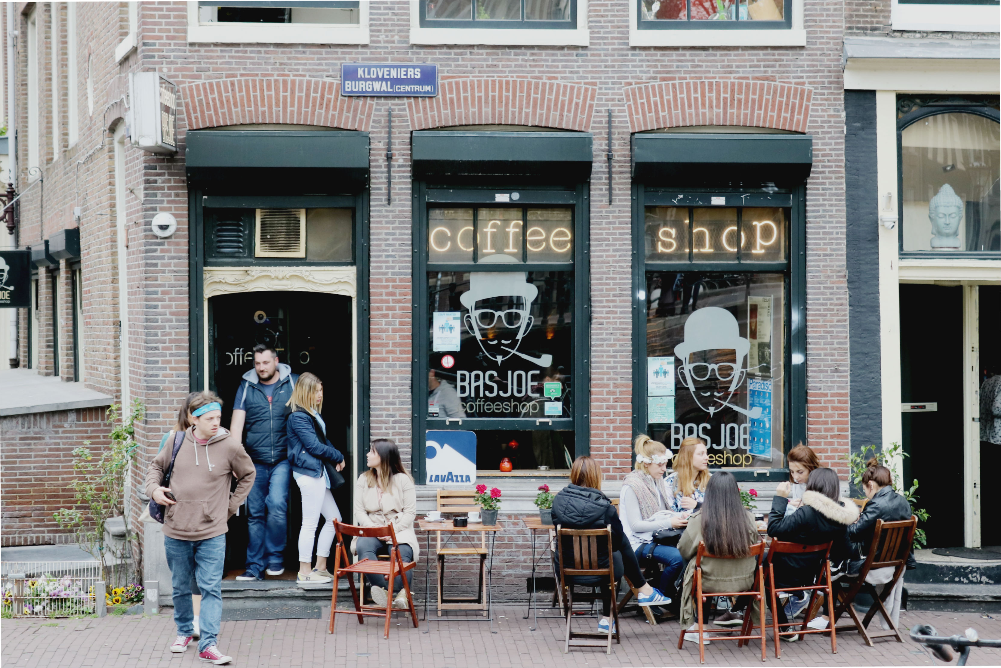 People sitting outside a coffee shop in Amsterdam