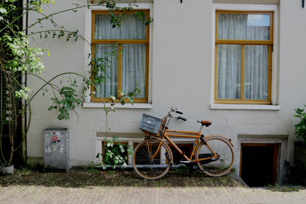orange bike leaned up against a house in amsterdam